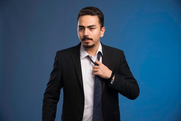 Zakenman in zwart pak zijn stropdas te nemen.