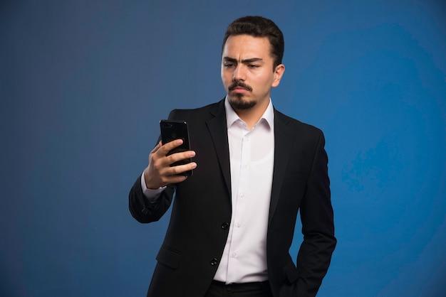 Zakenman in zwart pak zijn telefoon controleren en denken.