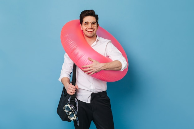 Zakenman in zwart-wit outfit en bril glimlacht terwijl hij rubberen ring en duikbril vasthoudt.