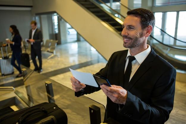 Zakenman instapkaart en paspoort houden