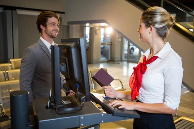 Zakenman interactie met vrouwelijk luchthavenpersoneel bij de incheckbalie