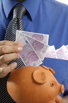Zakenman invoegen 500 euro bankbiljetten in spaarvarken