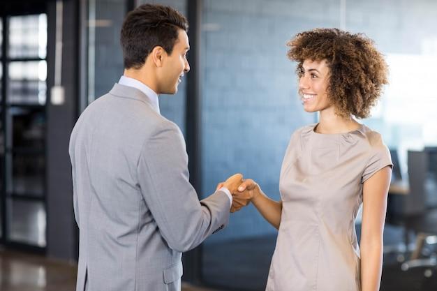 Zakenman jonge vrouw handen schudden in office