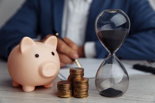 Zakenman keurt belangrijk contract in functie goed. roze spaarvarken met stapel muntstukken en zandloper op bureau. tijd is geld