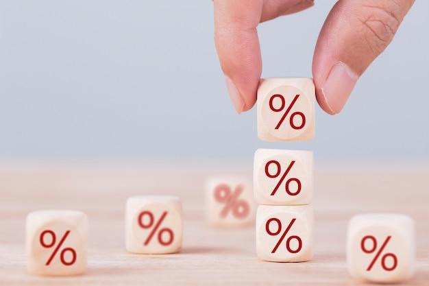 Zakenman kiest een houten kubusblok bovenop met procenttekenpictogram