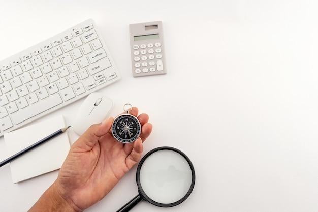 Zakenman kijken naar een kompas dat hij in zijn hand houdt, zakenman met een kompas in de hand houden op zakelijke objecten witte tabel achtergrond.