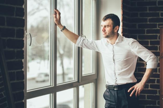 Zakenman kijkt door een raam vanuit zijn kantoor.
