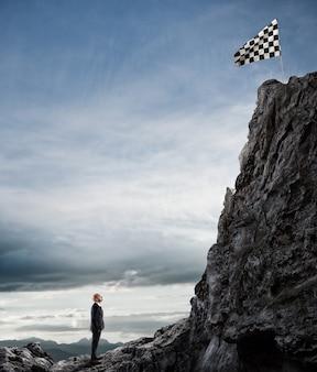 Zakenman kijkt naar een vlag op de bergtop. bedrijfsconcept zakenman overwint de problemen