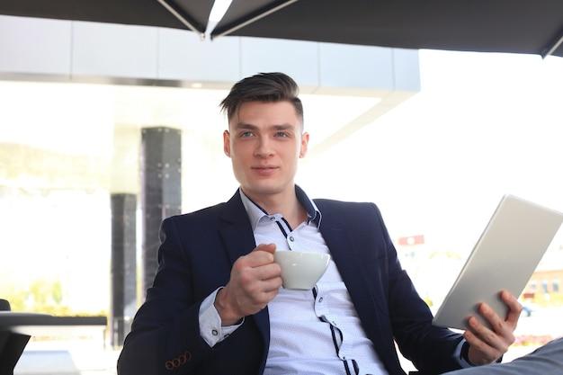 Zakenman koffie drinken en nieuws lezen in café.