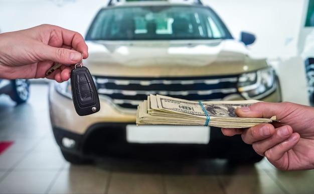 Zakenman koopt nieuwe auto in showroom die dollarsgeld geeft en sleutels neemt van auto, financiënconcept