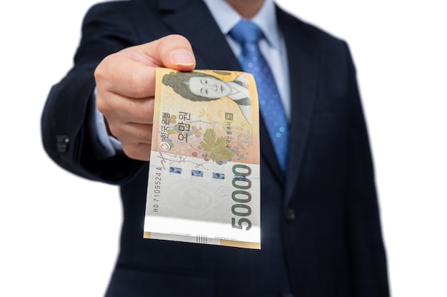 Zakenman koreaanse munt in de hand te houden.