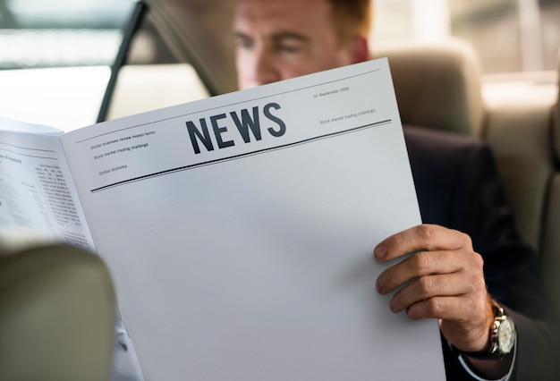 Zakenman lezing krant auto binnen