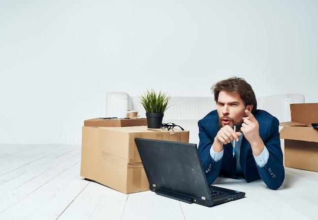Zakenman liggend op de vloer voor laptop werk kantoor in beweging