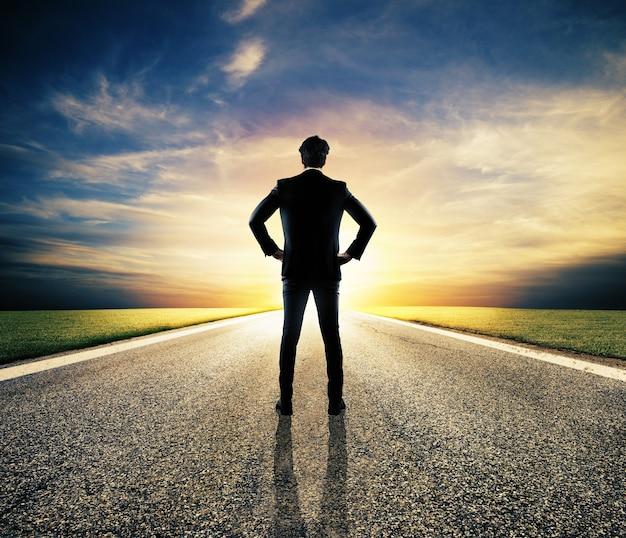 Zakenman loopt op een onbekende weg voor een nieuw avontuur bij zonsondergang