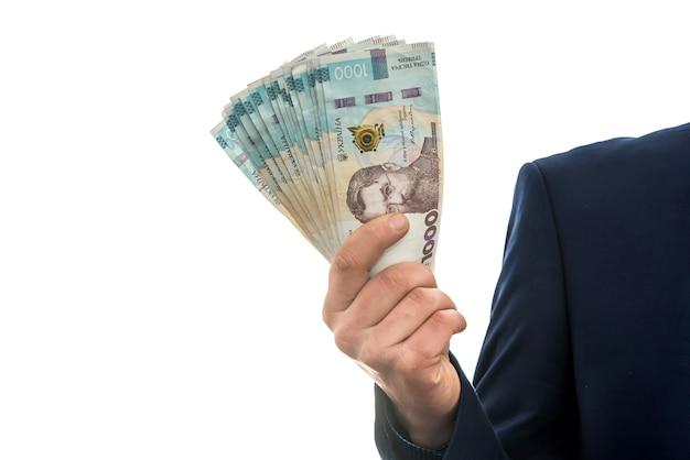 Zakenman maakte enorme winsten en toonde veel geld. een man in een pak houdt een pak nieuwe banktons van oekraïne vast. 1000 grivna