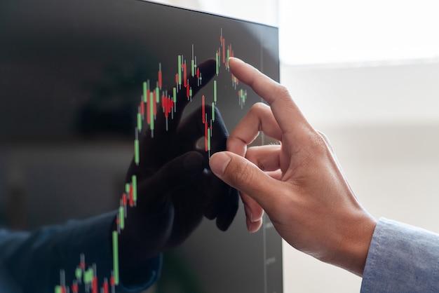 Zakenman makelaar analyseren financiële gegevens grafieken en rapporten op het scherm