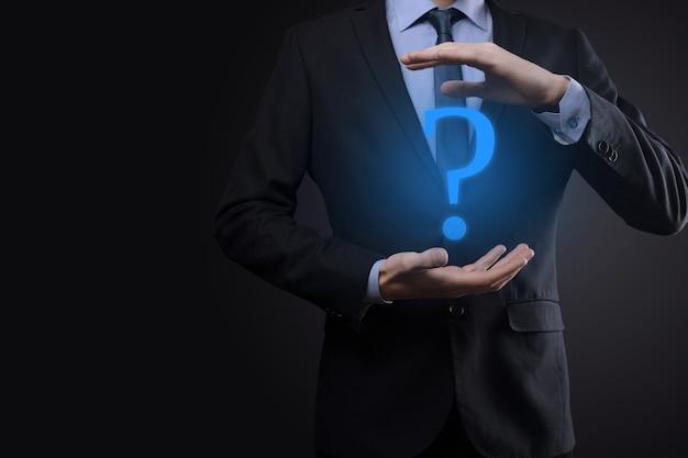 Zakenman man hand houden interface vraagtekens teken web. vraag quiestion online, faq-concept, wat waar, wanneer hoe en waarom, zoek informatie op internet.