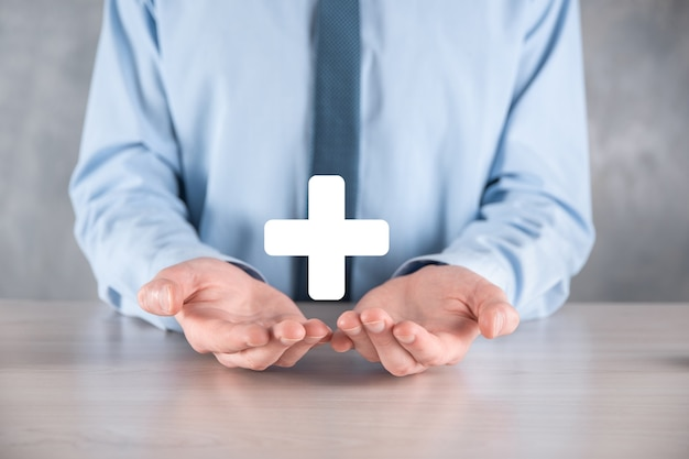 Zakenman, man in de hand houden bieden positieve dingen zoals winst, voordelen, ontwikkeling, mvo vertegenwoordigd door plusteken. de hand toont het plusteken.
