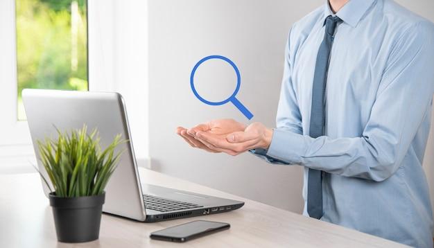 Zakenman, man in de hand houden vergrootglas icon.business, technologie en internet concept