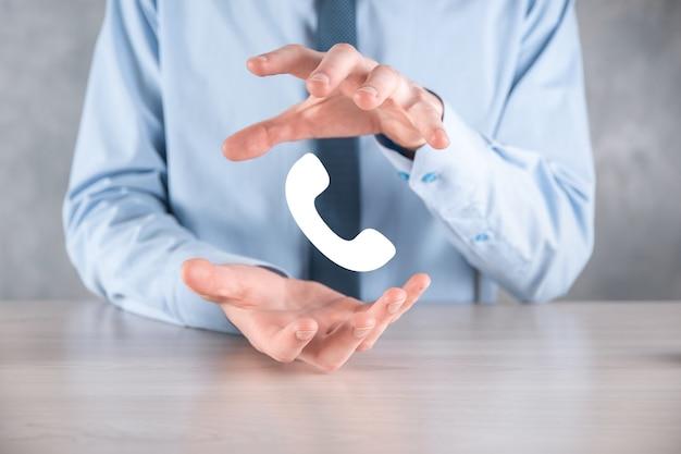 Zakenman man in een overhemd met een stropdas op grijze muur houden telefoonpictogram. bel nu business communication support center customer service technology concept.