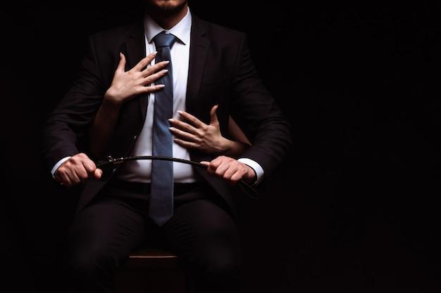Zakenman man in een pak met een leren zweep zit in een stoel terwijl de onderdanige persoon haar armen om hem heen slaat