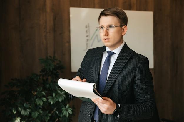 Zakenman man in glazen, schrijft het papierwerk op kantoor. zelfverzekerde professionele uitstraling. kantoorwerk.