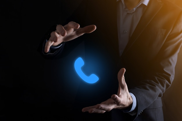 Zakenman man in pak houden telefoonpictogram. bel nu business communication support center customer service technology concept.