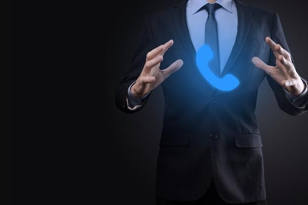 Zakenman man in pak op zwarte muur houden telefoonpictogram. bel nu business communication support center customer service technology concept.