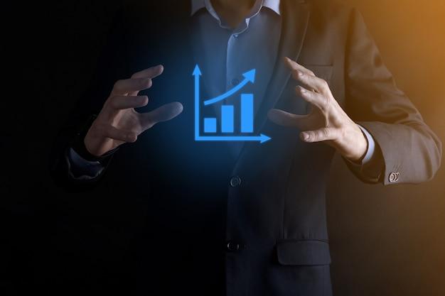 Zakenman man met een grafiek met positieve winstgroei. grafiekgroei en toename van grafiekpositieve indicatoren in zijn bedrijf plannen. winstgevender en groeiend.