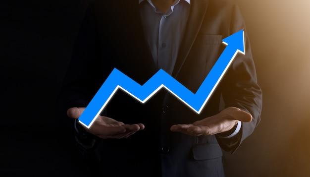 Zakenman man met een grafiek met positieve winstgroei. plan grafiekgroei en toename van grafiekpositieve indicatoren in zijn bedrijf. meer winstgevend en groeiend.