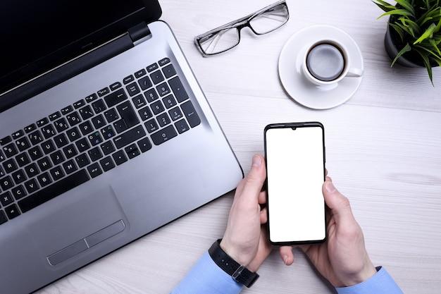 Zakenman, man werkt op desktop op laptop en maakt gebruik van mobiele telefoon