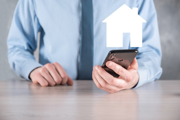 Zakenman mannelijke hand met huisje op blauwe achtergrond. vastgoedverzekering en veiligheidsconcept. onroerend goed concept. banner met kopie ruimte.