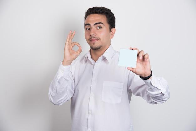 Zakenman memoblokken houden en ok teken op witte achtergrond tonen.