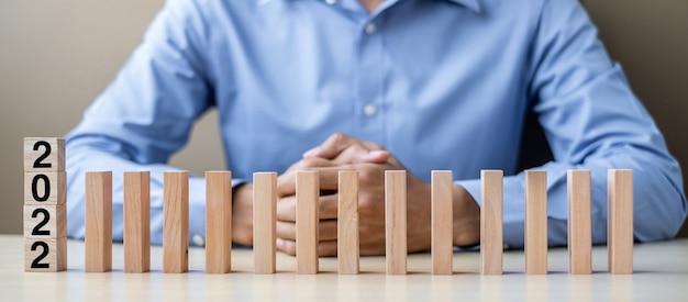 Zakenman met 2022 houten blokken. zakelijk, risicobeheer, verzekering, resolutie, strategie, oplossing, doel, nieuwjaar new you en gelukkige vakantieconcepten