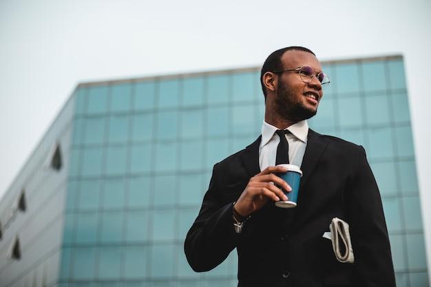 Zakenman met afhaalkoffie voor de wolkenkrabber. zwarte etnische man in jasje en stropdas