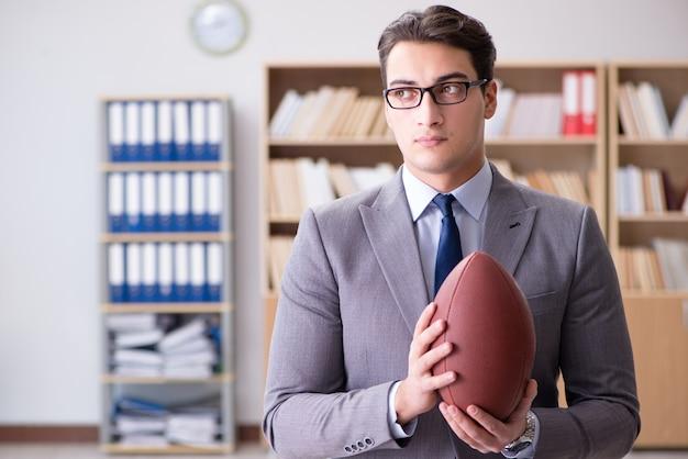 Zakenman met amerikaans voetbal in bureau