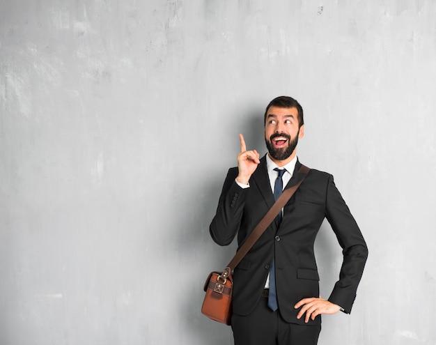 Zakenman met baard die de oplossing probeert te realiseren terwijl het opheffen van een vinger