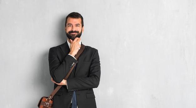 Zakenman met baard die en aan de voorzijde met zeker gezicht glimlacht kijkt