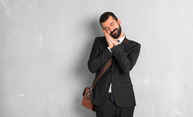 Zakenman met baard die slaapgebaar in dorable uitdrukking maakt