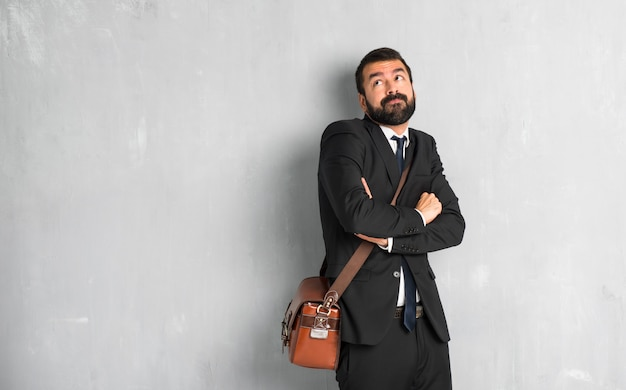 Zakenman met baard die twijfelsgebaar maken terwijl het opheffen van de schouders