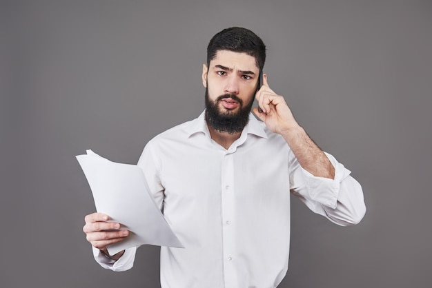 Zakenman met baard in wit overhemd met documenten en telefoon op grijze achtergrond.