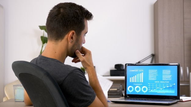 Zakenman met baard werkt hard aan zijn bureau op kantoor. gemotiveerde jongeman.