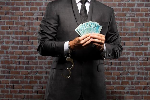 Zakenman met bankbiljetten met een handboei in een gevangenis. concept van corruptie, corrupte politici, illegale bedrijven. baksteen achtergrond.