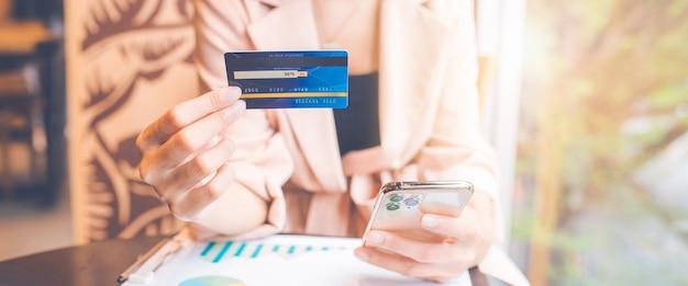 Zakenman met behulp van blauwe creditcard en mobiele telefoon online winkelen. voor webbanner.