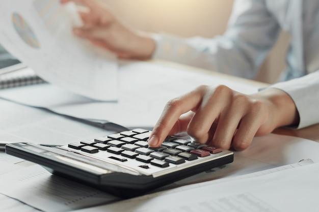 Zakenman met behulp van calculator voor het berekenen van de begroting op tafel in het kantoor