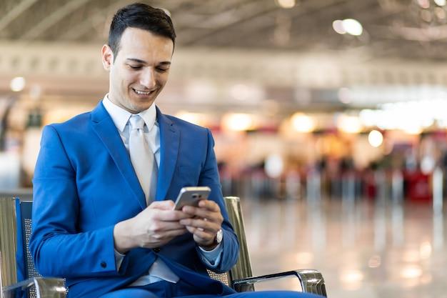 Zakenman met behulp van de telefoon op de luchthaven
