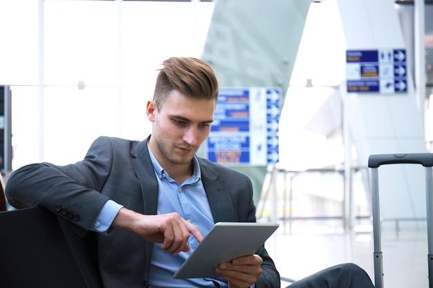 Zakenman met behulp van digitale tablet in de vertrekhal van de luchthaven.