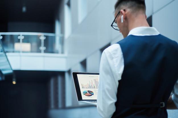 Zakenman met behulp van een laptop om financiële gegevens te controleren.