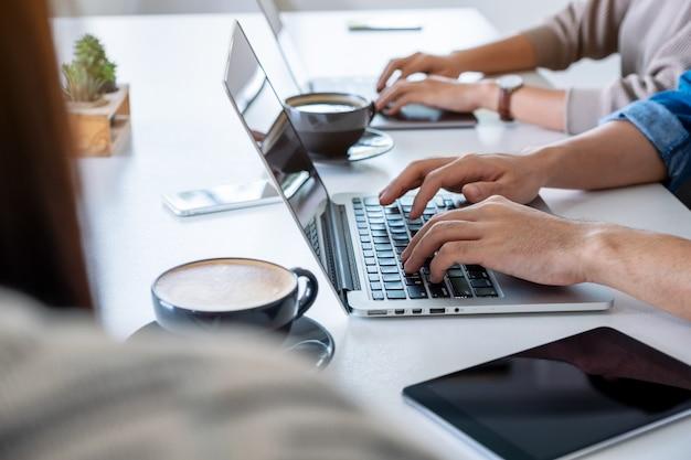 Zakenman met behulp van en werken op laptopcomputer met tablet pc op de tafel in office