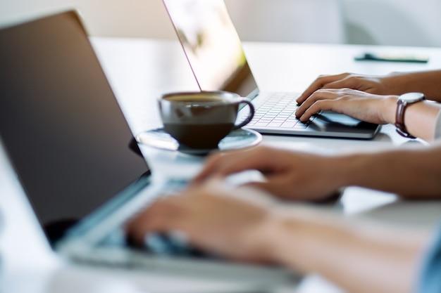 Zakenman met behulp van en werken op laptopcomputer samen in office